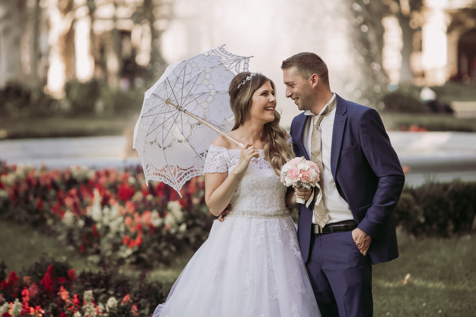The newlyweds laugh and watch as she holds her umbrella