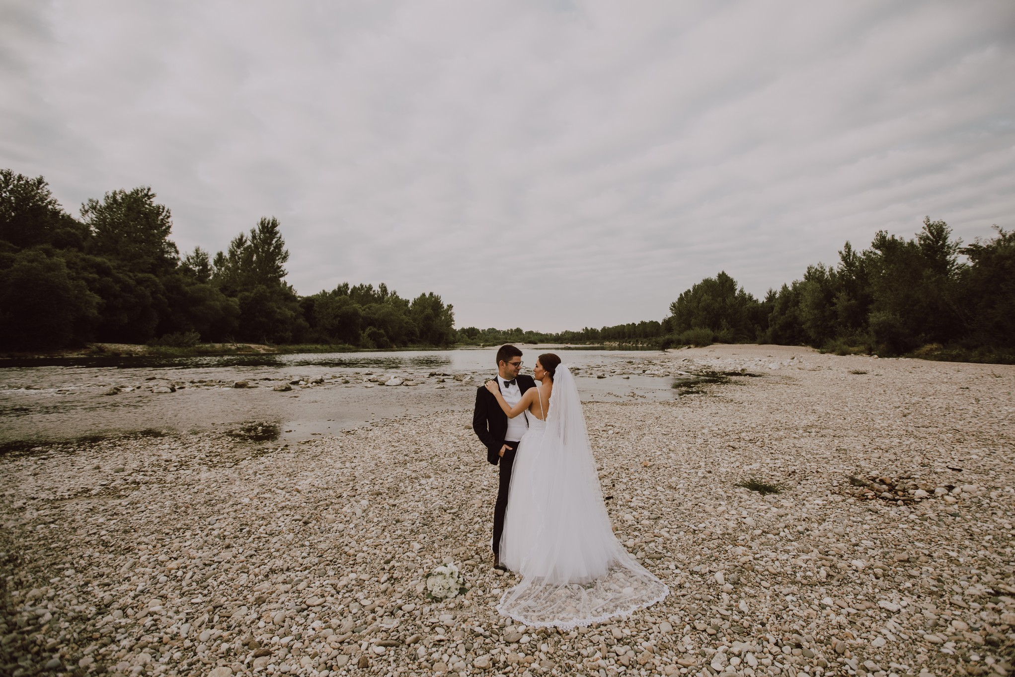 The couple stands on the riverbank and look at each other in love