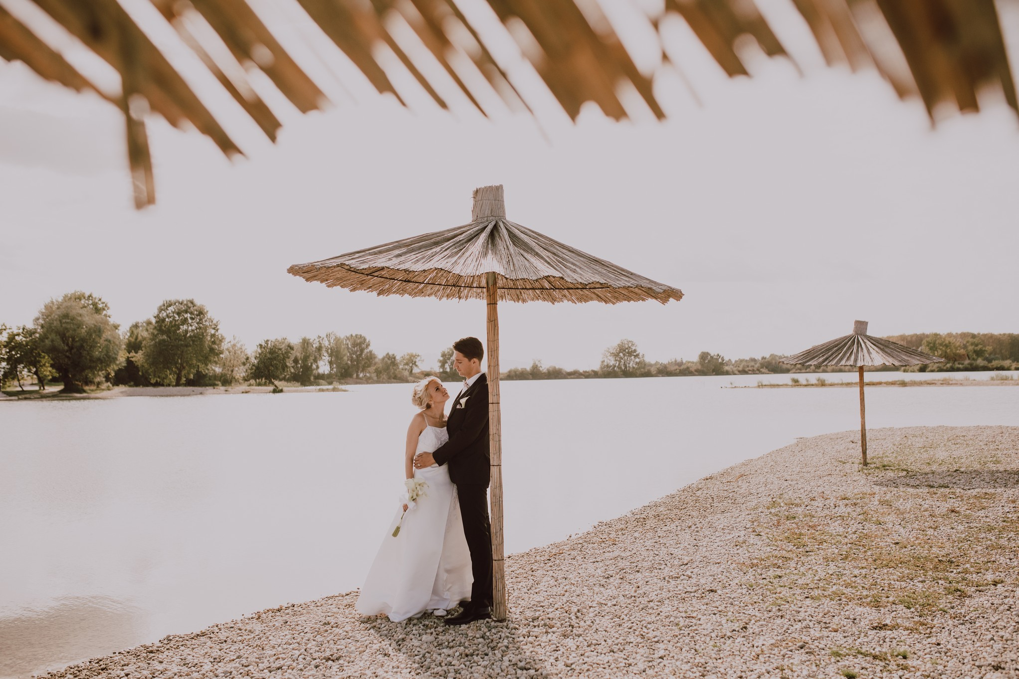 The couple stands by the lake under an umbrella and they look at each other in love