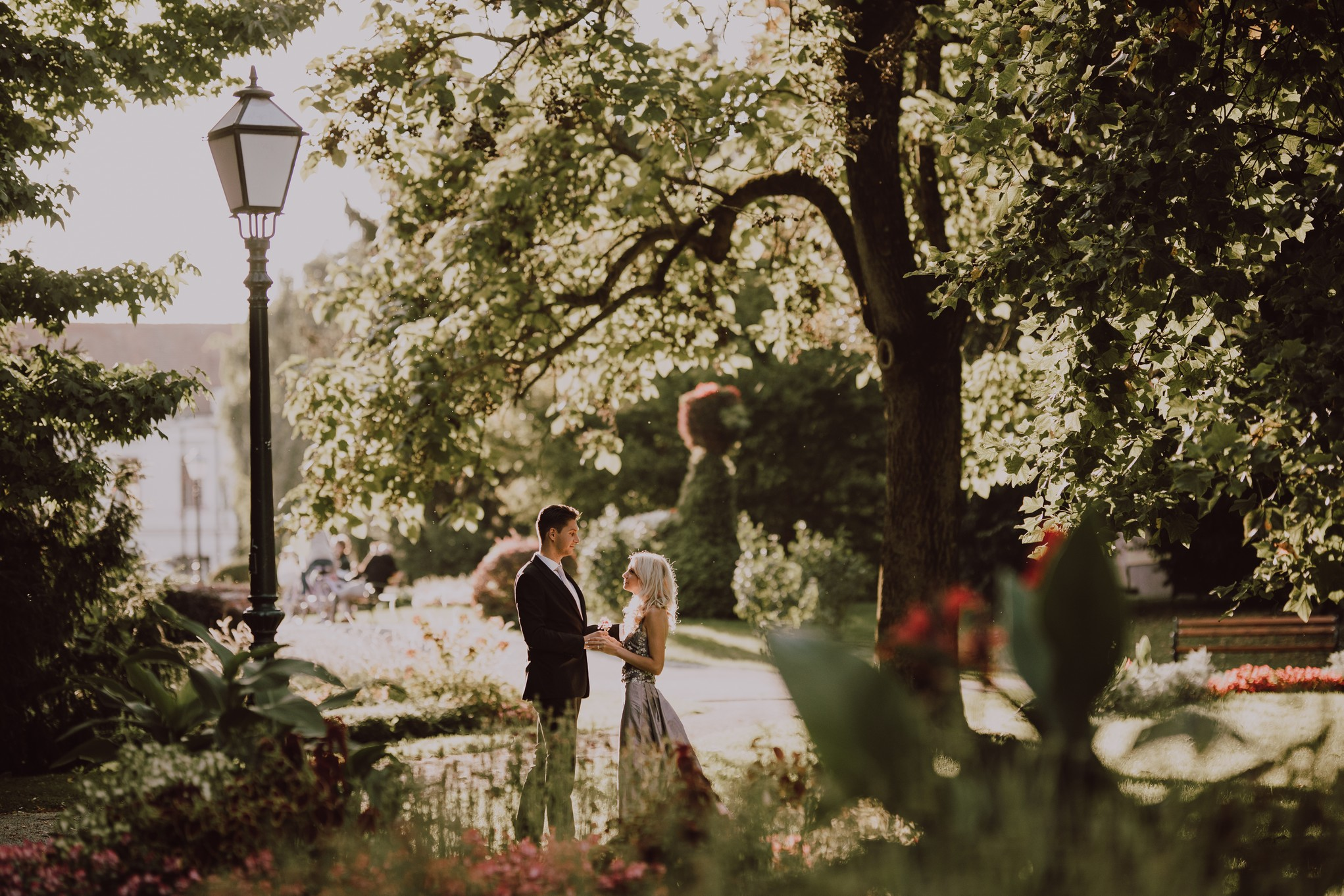 A couple of brides are standing in the park and looking at each other in love