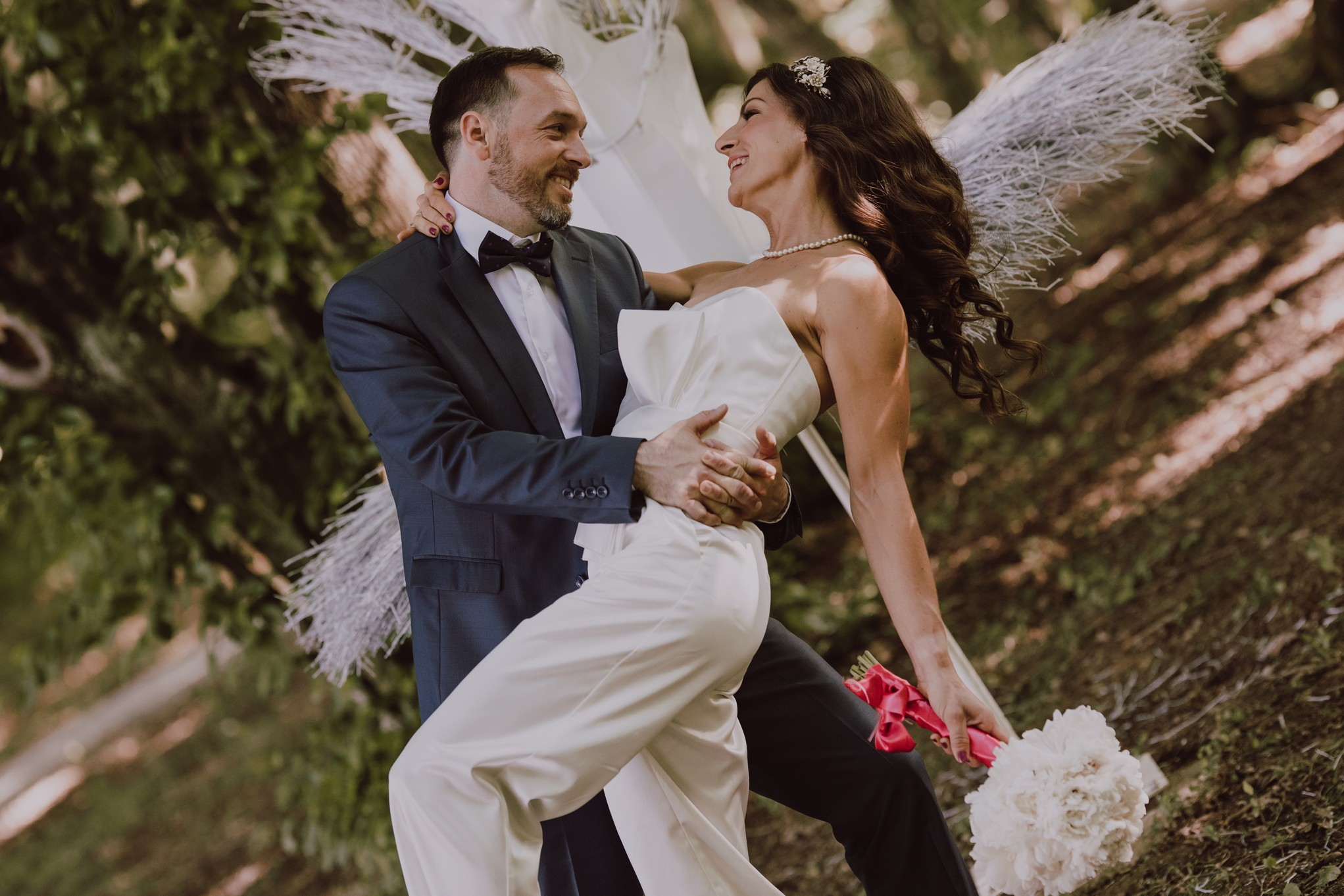Beautiful newlyweds are hugged in nature as she holds a wedding bouquet